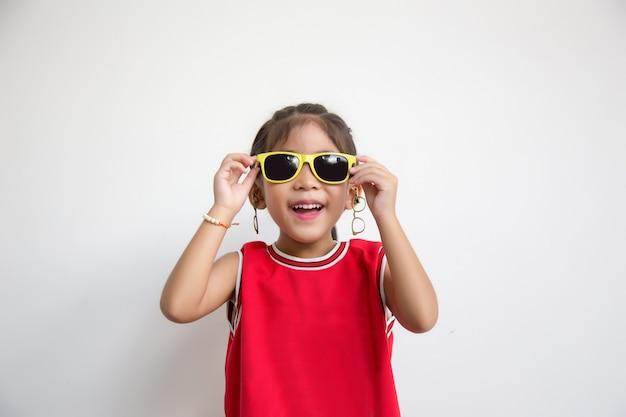 Asiatisches kind mit sporthemd- und sonneglasmode