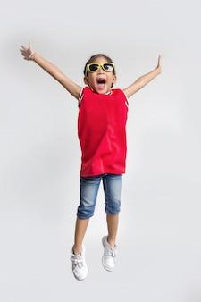Asiatisches kind mit springender aktion der sporthemd- und sonneglasmode