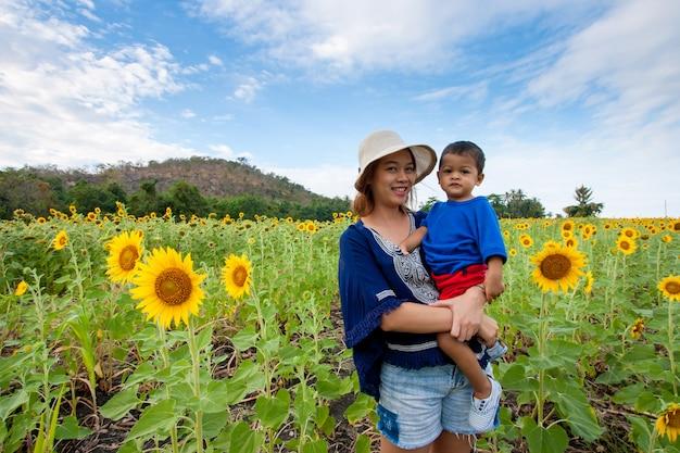 Asiatisches kind oder baby und glückliche junge mutter in der sonnenblumenwiese.