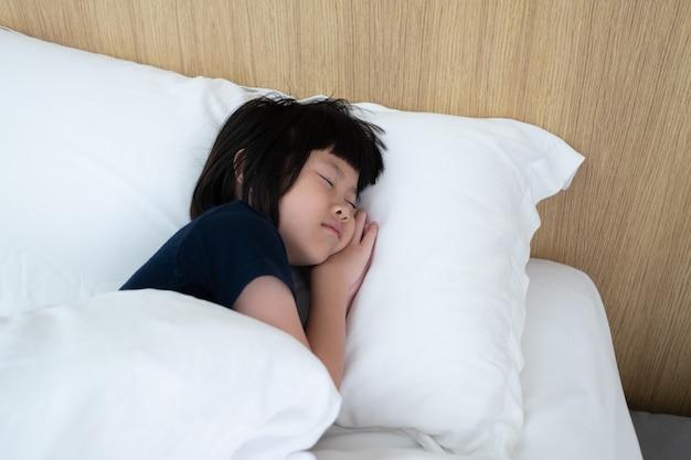 Asiatisches kind schlafen auf dem bett, krankes kind