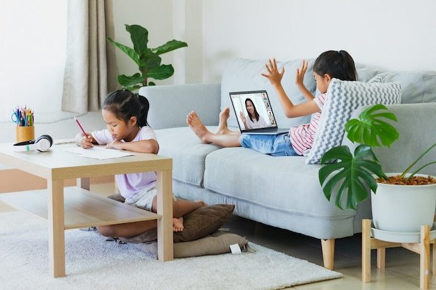 Asiatisches kind sitzt auf dem sofa und hat videokonferenz-chat mit lehrer und klassengruppe mit schwester, die arbeitsblatt nebenher macht. kinder lernen während der quarantäne aufgrund des covid-19-ausbruchs von zu hause aus.