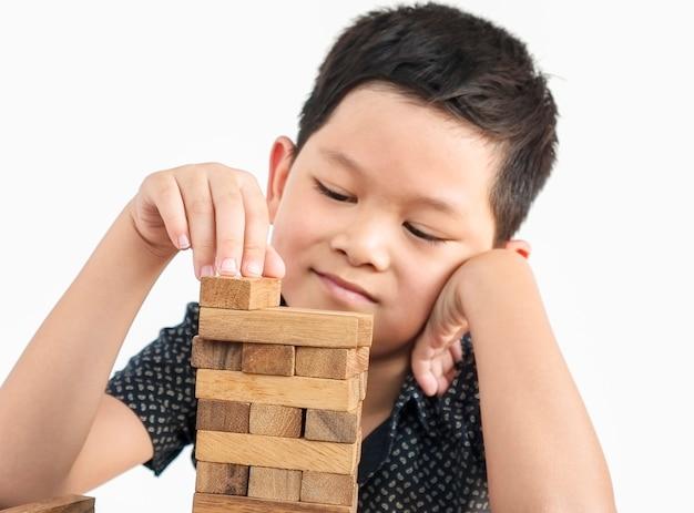 Asiatisches kind spielt jenga, ein turmspiel aus holzblöcken