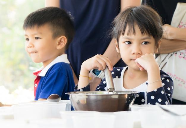 Asiatisches kind und familie lernen, wie man in einem kochkurs eiscreme macht.
