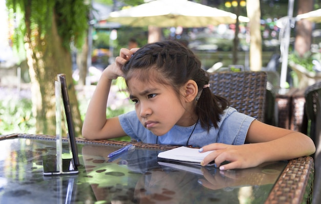 Asiatisches kind verwechselt mit e-learning beim lernen von zu hause in der pandemie mit einem mobiltelefon mit digitalen inhalten
