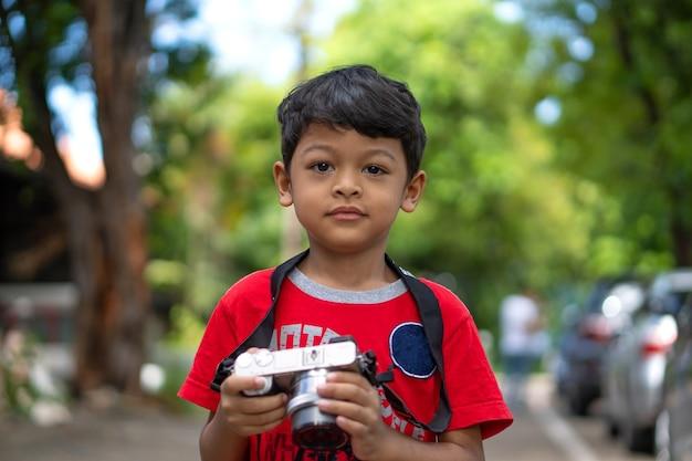 Asiatisches kind verwendet digitalkamera, die foto im öffentlichen park macht