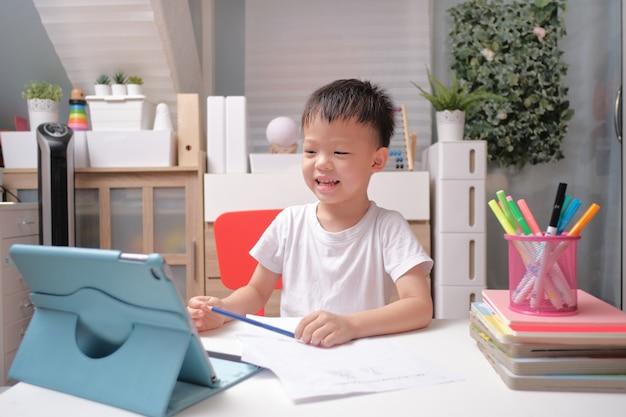 Asiatisches kind verwendet tablet-tablet, um seine online-lektion zu hause zu lernen