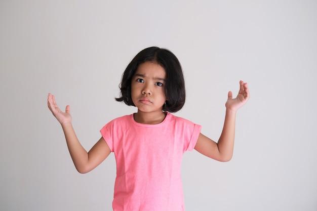 Asiatisches kind zeigt verärgerten gesichtsausdruck mit erhobenen händen