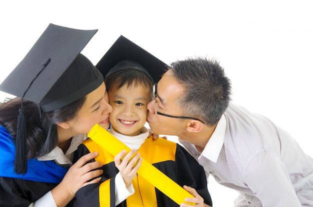 Asiatisches kindergartenkind im staffelungskleid und in der doktorhut geküsst von ihrem elternteil während der staffelung
