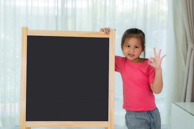 Asiatisches kindergartenmädchenkind, das tafel im schulraum schaut glücklich mit dem großen lächeln tut okayzeichen, daumen oben mit den fingern, ausgezeichnetes zeichen hält. zurück zu schule und bildungskonzept.
