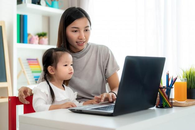 Asiatisches kindergartenschülerin mit muttervideokonferenz e-learning mit lehrer auf laptop im wohnzimmer zu hause. homeschooling und fernunterricht, online, bildung und internet.