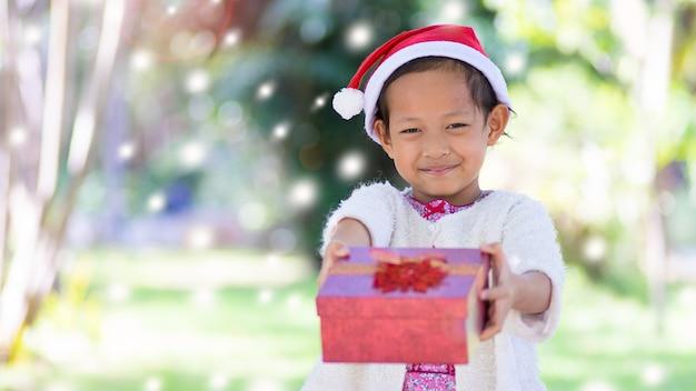 Asiatisches kinderkleines mädchen im roten hut sankt mit geschenkbox im naturhintergrund