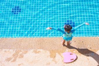 Asiatisches Kindermädchen im Badeanzug, der sich hin- und herbewegende Schaumseite das Pool steht und hält.