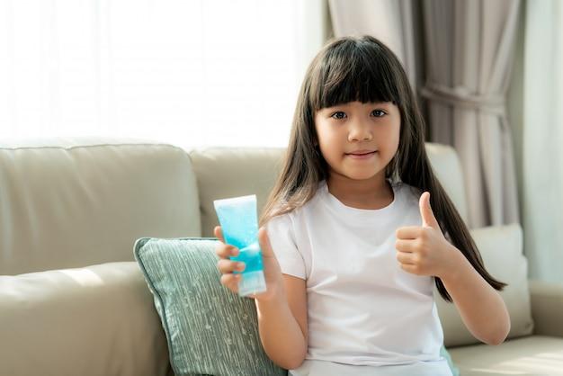 Asiatisches kindermädchen, das alkoholantiseptisches gel verwendet