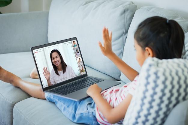 Asiatisches kindermädchen, das auf dem sofa sitzt und videokonferenz-chat mit lehrer und klassengruppe hat. das kind lernt während der quarantäne aufgrund des ausbruchs des coronavirus covid-19 von zu hause aus.