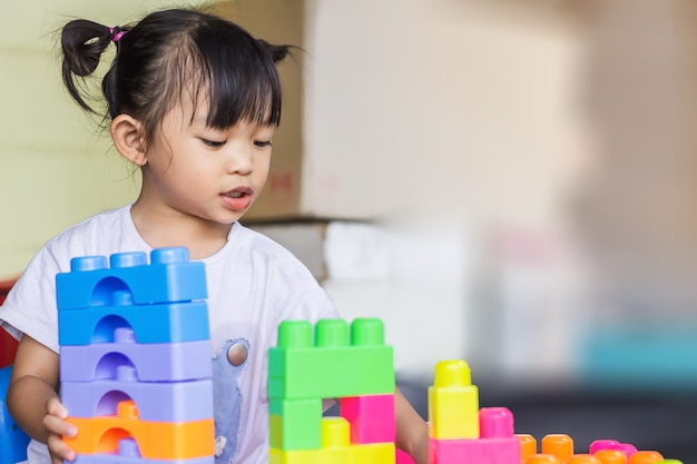 Asiatisches kindermädchen, das das plastikblockspielzeug spielt lern- und bildungskonzept lächelndes kleines baby