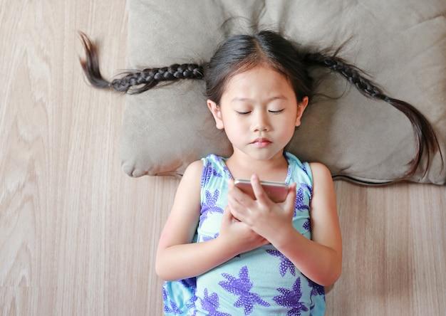 Asiatisches kindermädchen, das den smartphone liegt auf bretterboden schaut. draufsicht