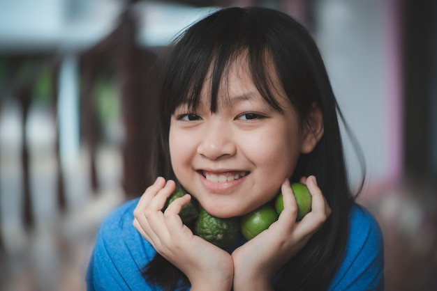 Asiatisches kindermädchen, das die limettenzitrone und bergamotte mit lächeln und glücklich hält, konzept von kräutern für antivirale und immun gegen den körper