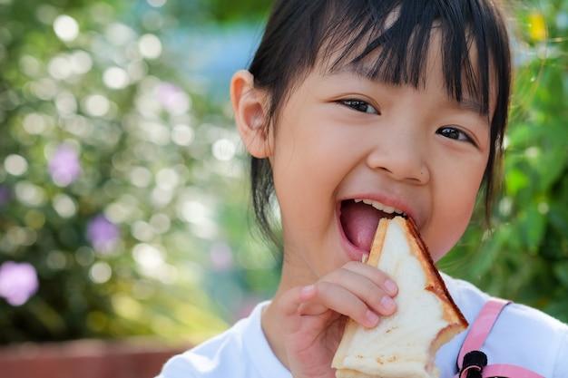 Asiatisches kindermädchen, das ein sandwich mit einem hellen lächeln isst