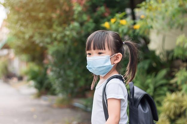 Asiatisches kindermädchen, das eine gesichtsmaske trägt und eine schultasche mitnimmt zurück zur schule und kind kindheit