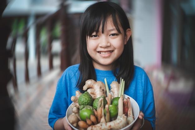 Asiatisches kindermädchen, das eine schüssel mit kräutern hält, umfasst viele arten wie ingwer, galgant, zitronengras, kaffir-limette, zitrone. kräuterkonzept für antivirale und immun gegen den körper