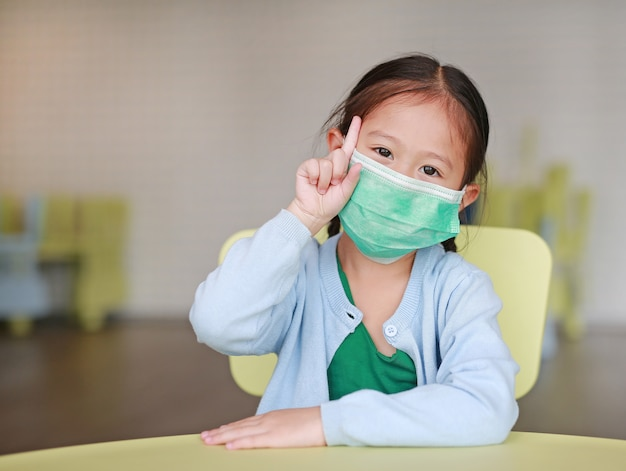 Asiatisches kindermädchen, das eine schutzmaske mit dem zeigen eines zeigefingers trägt