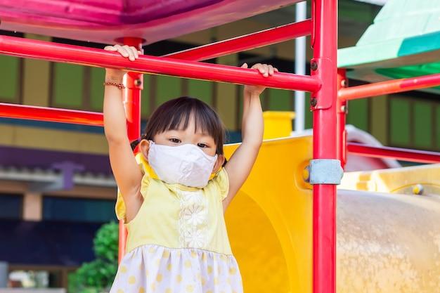 Asiatisches kindermädchen, das eine stoffgesichtsmaske trägt, wenn sie ein spielzeug am spielplatz spielt. soziale distanz.