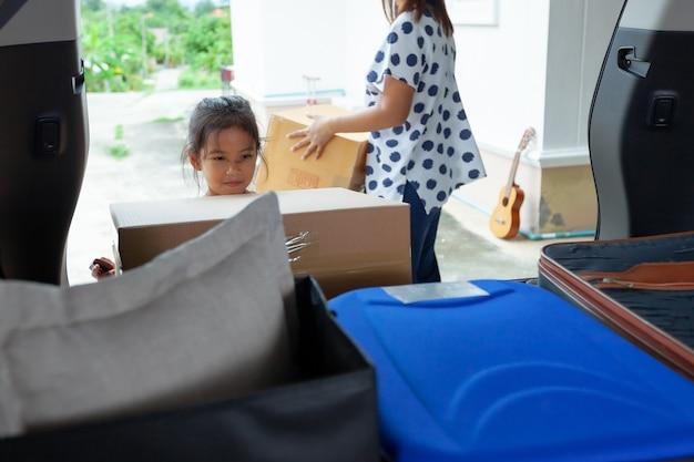 Asiatisches kindermädchen, das eltern hilft, einen karton mit sachen zu tragen, die in das auto bewegen