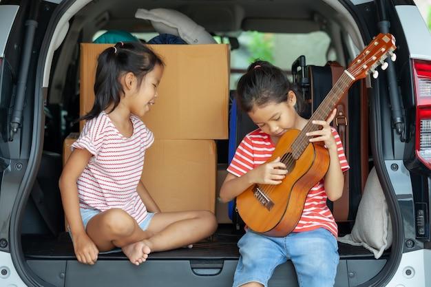 Asiatisches kindermädchen, das gitarre spielt und ein lied mit ihrer schwester in einem autokofferraum singt