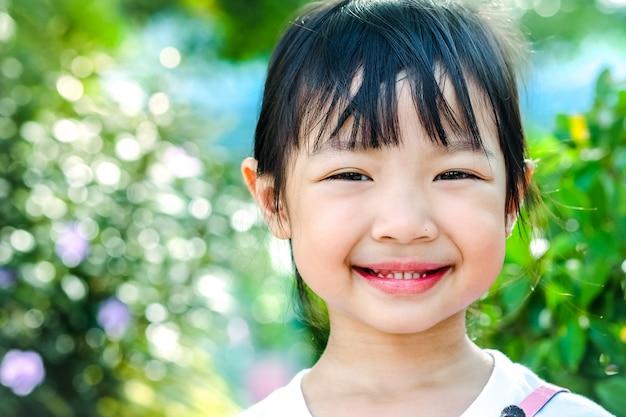 Asiatisches kindermädchen, das hell mit glück lächelt.