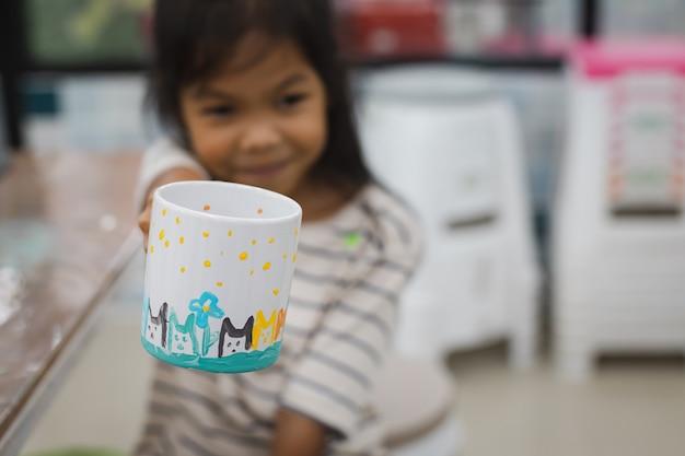 Asiatisches kindermädchen, das ihre eigene arbeit nach fertiger farbe auf keramikglas mit ölfarbe zeigt. kreative aktivitätsklasse für kinder in der schule.