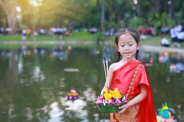 Asiatisches kindermädchen, das krathong in teich für verzeihung göttin ganges-festival in thailändischem schwimmt