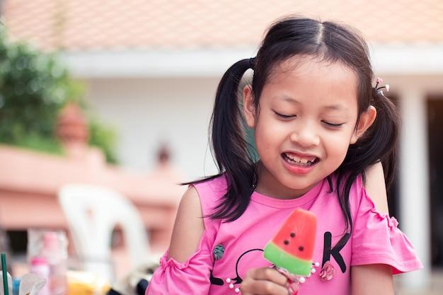 Asiatisches kindermädchen, das mit dem essen der eiscreme lächelt und glücklich ist