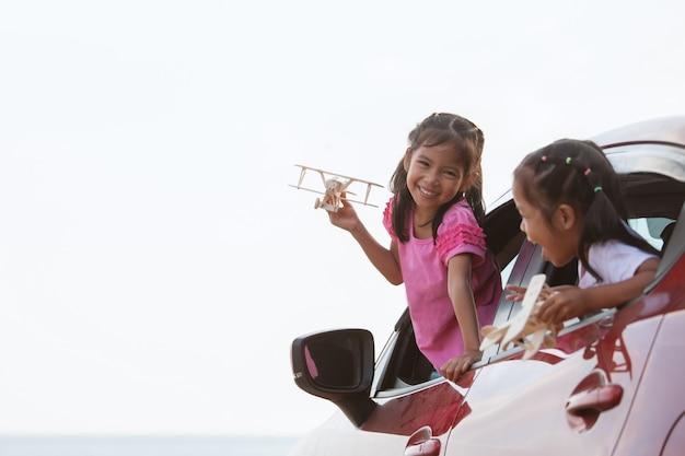 Asiatisches kindermädchen, das mit hölzernem flugzeug des spielzeugs mit ihrer schwester während reise mit dem auto spielt