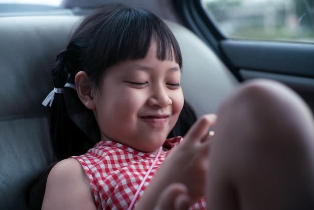 Asiatisches kindermädchen, das mit smartphone im auto spielt