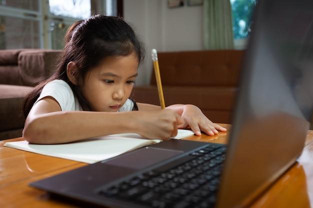 Asiatisches kindermädchen, das notizbuch verwendet, um online-technologie zu hause zu lernen. konzept der online-bildung, des sozialen fernunterrichts zu hause während der quarantäne und der schulferien.