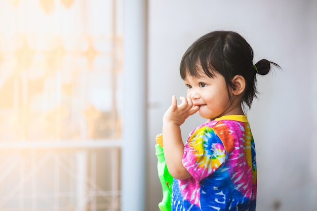Asiatisches kindermädchen, das spaß hat, wasser mit wasserwerfer in songkran-festival thailand zu spielen