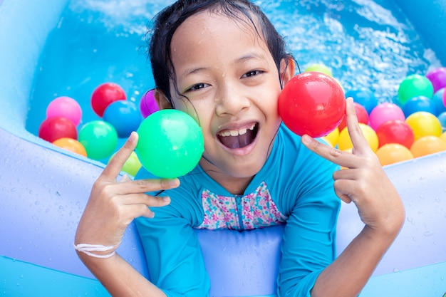 Asiatisches kindermädchen, das spaß im garten-planschbecken mit farbball hat