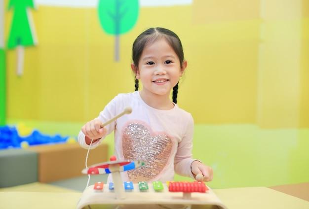 Asiatisches kindermädchen, das spaß mit spielwaren, musikinstrumente hat.