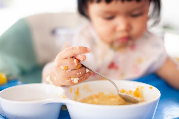 Asiatisches kindermädchen des netten babys, das gesundes lebensmittel durch isst und eine verwirrung bildet