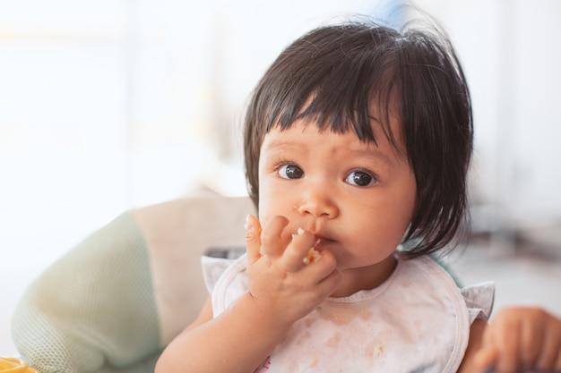 Asiatisches kindermädchen des netten babys, das gesundes lebensmittel durch isst