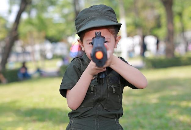 Asiatisches kindermädchen im pilotsoldat-klagenkostüm mit schießgewehr im garten.