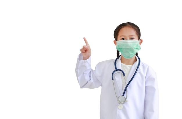 Asiatisches kindermädchen in der medizinischen uniform zeigt zeigefinger nach oben. porträt des kleinen kindes mit stethoskop beim tragen der arztuniform und der medizinischen maske lokalisiert auf weißem hintergrund