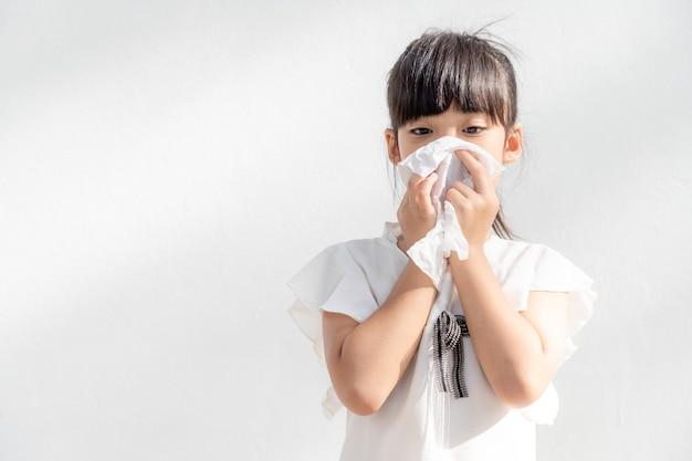 Asiatisches kindermädchen krank mit niesen in die nase und kaltem husten auf seidenpapier, weil schwach