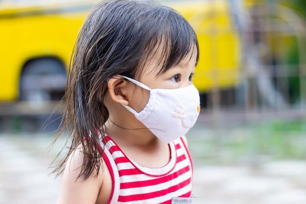 Asiatisches kindermädchen lächelnd und stoffmaske tragend,