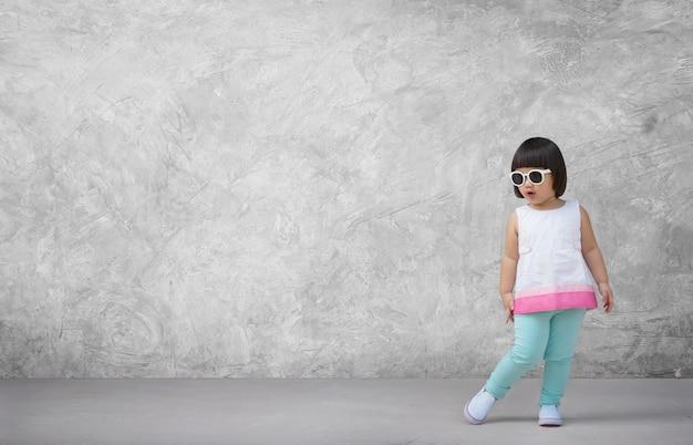 Asiatisches kindermädchen mit betonmauer im leeren raum.
