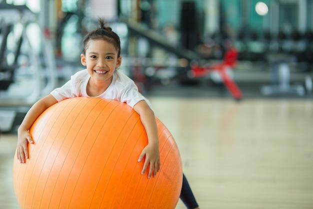 Asiatisches kindermädchen mit gymnastikball