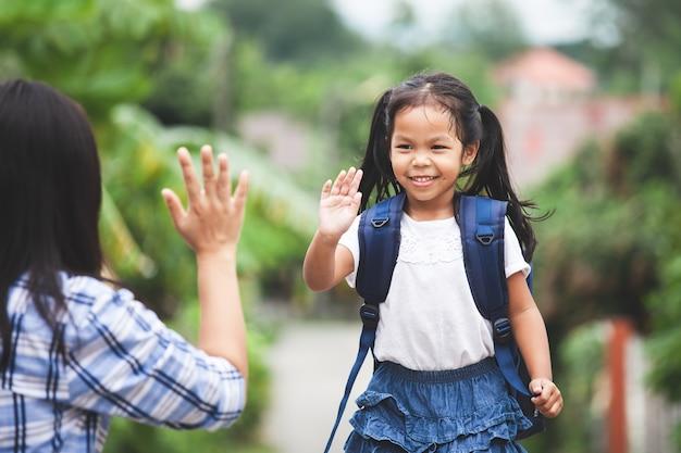 Asiatisches kindermädchen mit schultasche und ihre mutter, die hallo geste fünf vor machen