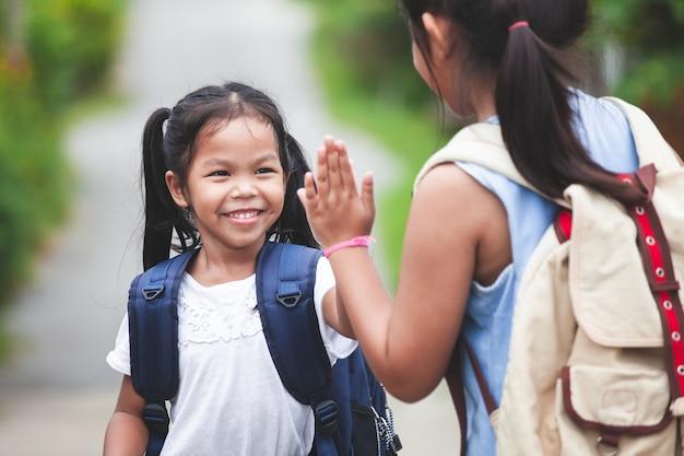 Asiatisches kindermädchen mit schultasche und ihrer älteren schwester, die hallo geste fünf macht