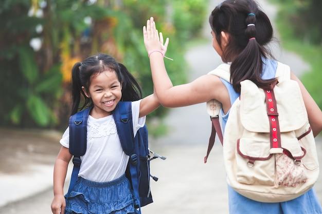 Asiatisches kindermädchen und ihre ältere schwester, die hallo fünf geste macht, bevor gehen zur schule