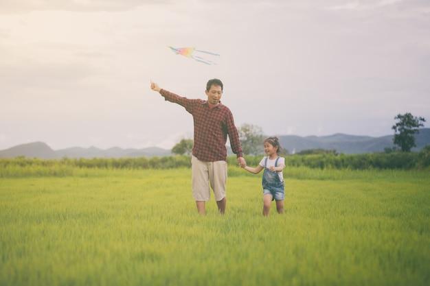Asiatisches kindermädchen und -vater mit einem drachen, der auf wiese im sommer in der natur läuft und glücklich ist